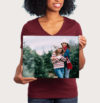Woman holding classic sized print of daughters in front of Christmas trees